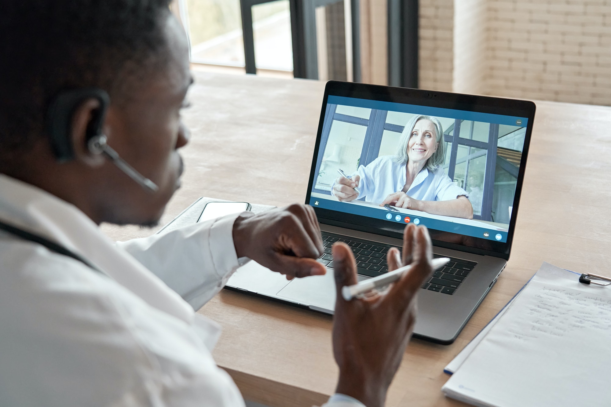Black male doctor consulting senior patient by telemedicine online video call.